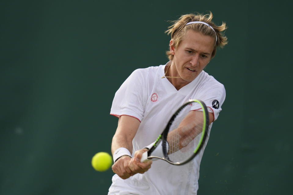 Sebastian Korda of the US plays a return to Antoine Hoang of France during the men's singles second round match on day three of the Wimbledon Tennis Championships in London, Wednesday June 30, 2021. (AP Photo/Kirsty Wigglesworth)