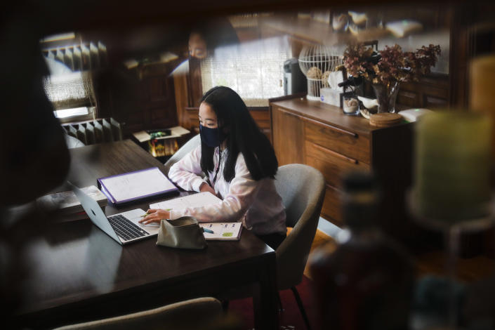 Lauren Choy, a sophomore at Boston Latin School, participates in her history class while sitting in her family's dining room in Jamaica Plain on Thursday afternoon. (Erin Clark/The Boston Globe via Getty Images)