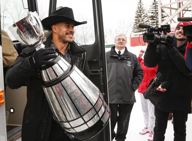 Calgary Stampeders' Jon Cornish holds the Grey Cup as he returns to Calgary, Alberta, Monday, Dec. 1, 2014, after defeating the Hamilton Tiger-Cats to win the 102nd Grey Cup. (AP Photo/The Canadian Press, Jeff McIntosh)