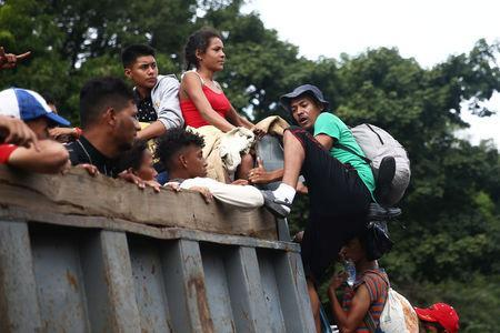 A Honduran migrant, part of a caravan trying to reach the U.S., climbs on a truck during a new leg of his travel in Zacapa, Guatemala October 17, 2018. REUTERS/Edgard Garrido