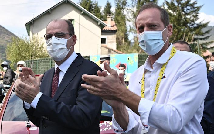 Tour de France Director Christian Prud'homme (1st-R) and French Prime Minister Jean Castex applaud the riders during the 8th stage of the 107th edition of the Tour de France cycling race, 140 km between Cazeres-sur-Garonne and Loudenvielle, on September 5, 2020 - Anne-Christine Poujoulat/AFP