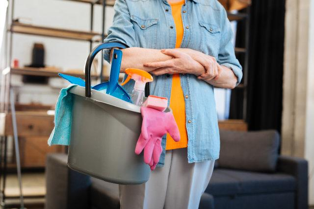 Hard-working mature woman in jeans jacket holding bucket