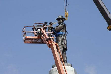 Construction workers attach a crane to a monument of Robert E. Lee, who was a general in the Confederate Army, before it is removed in New Orleans