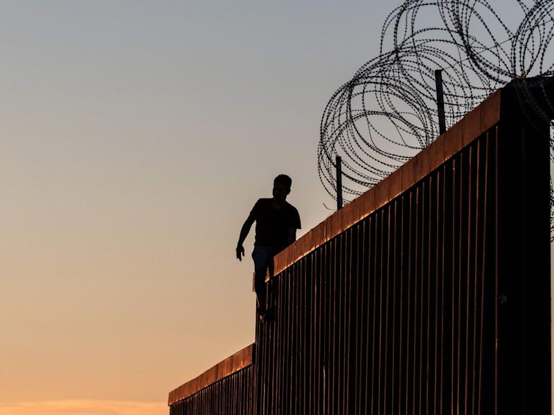 A man walks along the top of the fence separating the US and Mexico in California: AFP/Getty Images