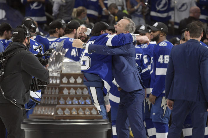 Tampa Bay Lightning head coach Jon Cooper is hugged by a player after the Lighting defeated the Montreal Canadiens in Game 5 of the NHL hockey Stanley Cup finals, Wednesday, July 7, 2021, in Tampa, Fla. (AP Photo/Phelan Ebenhack)