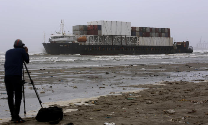 A cameraman films the stranded Heng Tong 77 cargo ship at Sea View Beach near the southern port city of Karachi, Pakistan, Monday, July 26, 2021. Pakistani authorities said they are working on plans to refloat the cargo ship that ran aground last week amid bad weather en route to Istanbul from China. (AP Photo/Fareed Khan)