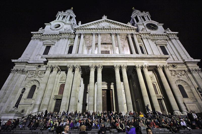 Supporters of the Occupy London Stock Exchange protest take part in a mass meditation on the steps of St Paul's Cathedral in London, Thursday, Oct. 27, 2011.  The senior St. Paul's Cathedral priest who welcomed anti-capitalist demonstrators to camp outside the London landmark resigned Thursday, saying he feared moves to evict the protesters could end in violence.  Other senior clergy and politicians urged the campers to leave peacefully, as the cathedral announced it would reopen to the public Friday after a weeklong closure triggered by the demonstrators' tents.  (AP photo/Matt Dunham)