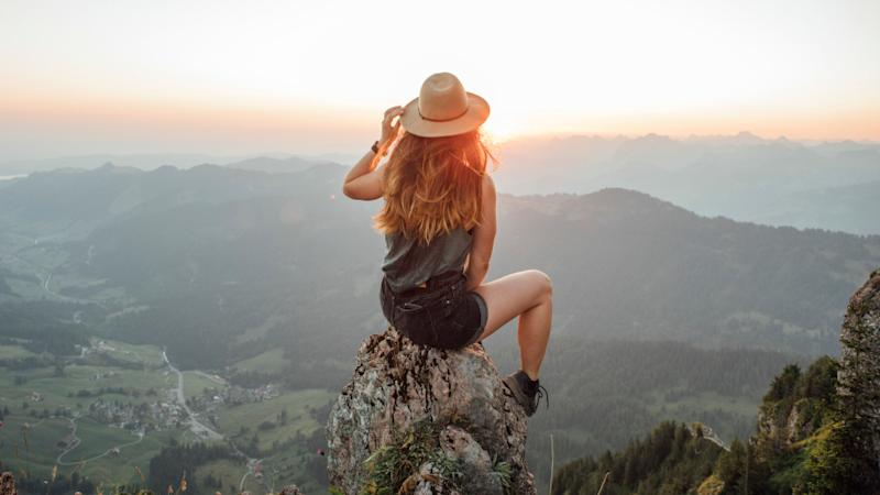 A young woman sitting on a rock at sunrise at Grosser Mythen, Switzerland.