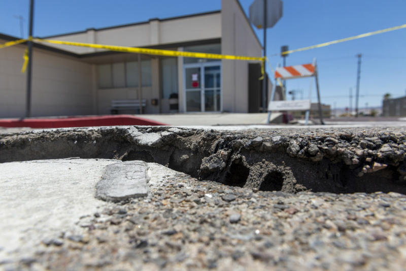 Damaged pavement from an earthquake surrounds the Searle Valley Domestic Water company in Trona, Calif., on Wednesday, July 10, 2019. The water company, the U.S. Post office building and a local restaurant were among the commercial buildings deemed unfit for occupancy after recent earthquakes. Residents of the little community of Trona gathered at a town hall Wednesday to hear officials give updates on the recovery. (James Quigg/The Daily Press via AP)