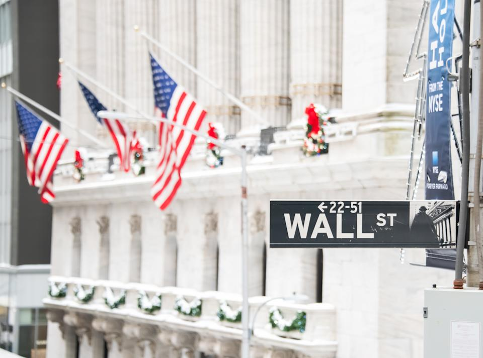 NEW YORK, NEW YORK - DECEMBER 18: The Wall Street street sign is visible against the New York Stock Exchange on December 18, 2020 in New York City. The pandemic has caused long-term repercussions throughout the tourism and entertainment industries, including temporary and permanent closures of historic and iconic venues, costing the city and businesses billions in revenue. (Photo by Noam Galai/Getty Images)