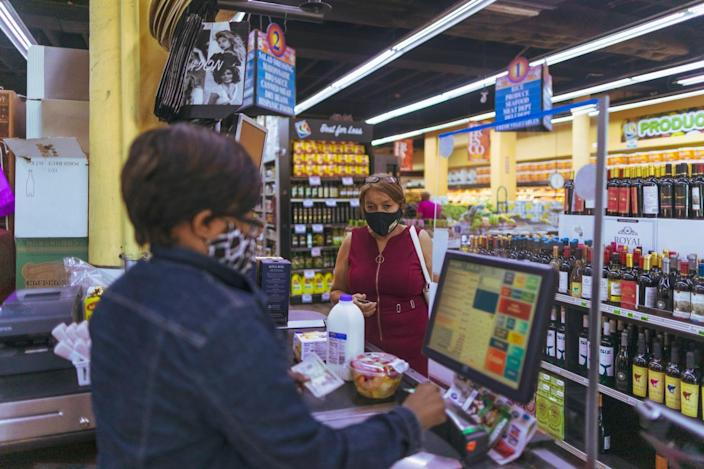Elsa Romero purchases a vanilla poundcake, fruit and milk at a discount grocer March 16 in Miami. For Romero, 57, the cake is a cheap alternative to her expensive insulin.