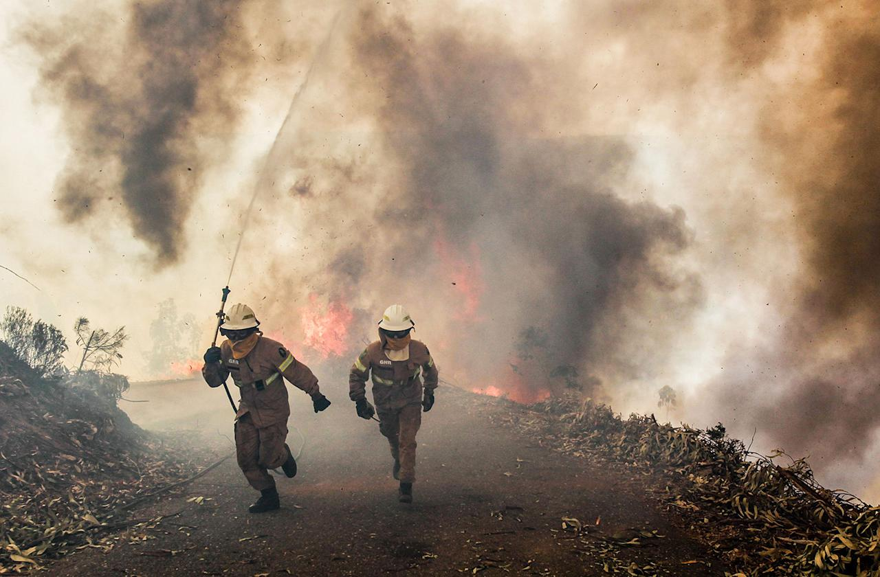 <p>Portuguese National Republican Guard firefighters run along a road as they battle a forest fire in Capela Sao Neitel, Alvaiazere, central Portugal, June 18, 2017. (Paulo Cunha/EPA/Rex/Shutterstock) </p>