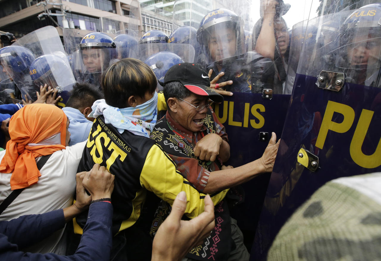 <p>Protesters scuffle with police during a rally near the U.S. Embassy in Manila to protest this weekend's visit of President Donald Trump on Saturday, Nov. 11, 2017 in Manila, Philippines. Trump is currently on a visit to Asia with the Philippines as his last stop for the ASEAN leaders' summit and related summits between the regional grouping and its Dialogue Partners. (Photo: Aaron Favila/AP) </p>