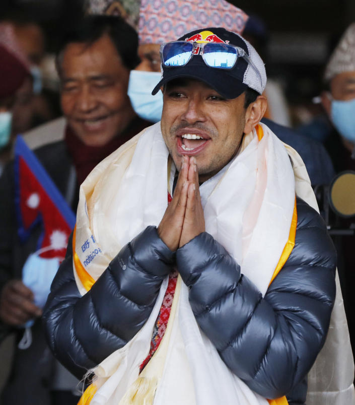 Nirmal Purja, one of the team member of the all-Nepalese mountaineering team that became the first to scale Mount K2 in winter greets as the team arrives at Tribhuwan International airport in Kathmandu, Nepal, Tuesday, Jan. 26, 2021. (AP Photo/Niranjan Shrestha)