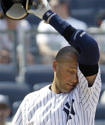 New York Yankees Derek Jeter wipes his face on his jersey inning during his seventh inning at-bat in the Yankees baseball game against the Chicago White Sox at Yankee Stadium in New York, Sunday, July 1, 2012. (AP Photo/Kathy Willens)