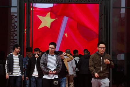 Visitors walk in front of a screen showing the Chinese national flag at an exhibition marking the 40th anniversary of China's reform and opening up at the National Museum of China in Beijing, China November 14, 2018. REUTERS/Thomas Peter