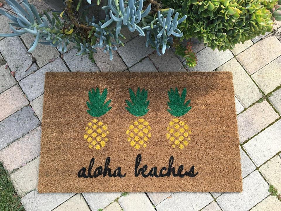 <p>Transport your home to a beach with the <span>Aloha Beaches Pineapple Doormat</span> ($46).</p>