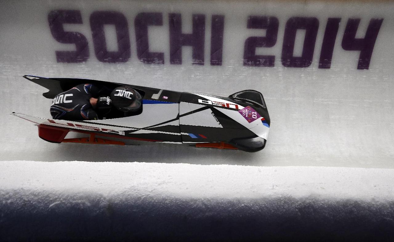 The team from the United States USA-1, piloted by Steven Holcomb and brakeman Steven Langton, take a curve during the men's two-man bobsled competition at the 2014 Winter Olympics, Monday, Feb. 17, 2014, in Krasnaya Polyana, Russia. (AP Photo/Natacha Pisarenko)