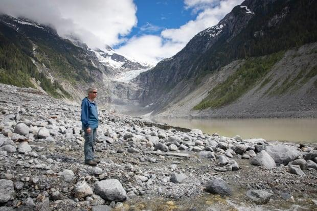 Brian Menounos, a professor of geography at the University of Northern British Columbia and Canada's research chair in glacier change, surveys a debris field caused by a landslide and outburst flood off the coast of B.C. in June.  (Briar Stewart/CBC News - image credit)
