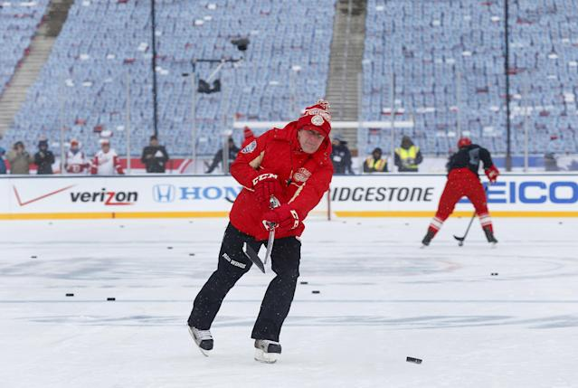 Detroit Red Wings head coach Mike Babcock shoots a puck during practice on the outdoor rink for the NHL Winter Classic hockey game against the Toronto Maple Leafs at Michigan Stadium in Ann Arbor, Mich., Tuesday, Dec. 31, 2013. The game is scheduled for New Year's Day. (AP Photo/Paul Sancya)