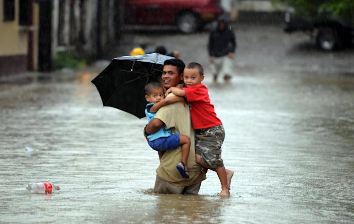 A man carries three children in a street flooded by the overflowing of Honduras' largest river, the Ulua, in El Progreso municipality on October 20, 2008, after heavy rains linked with El Nino (AFP Photo/Orlando Sierra)