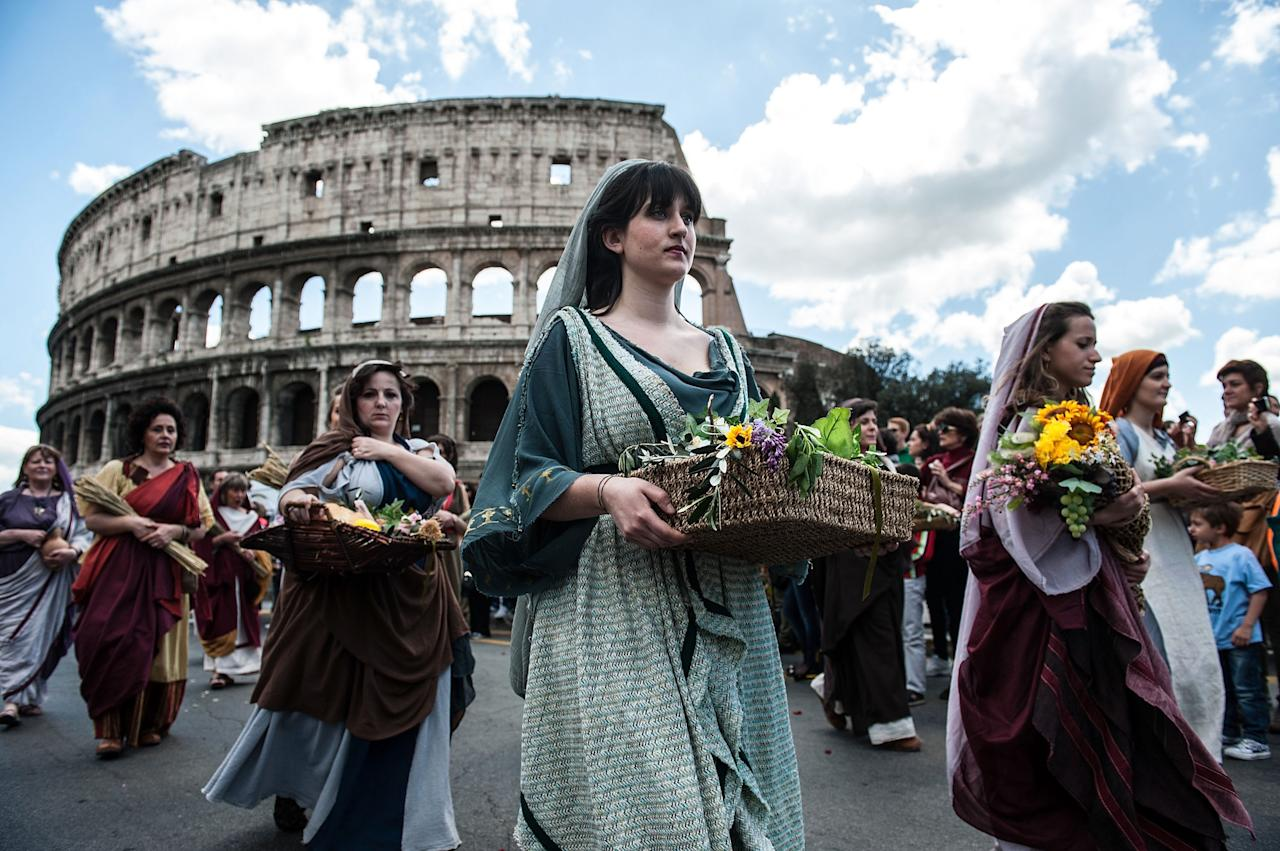ROME, ITALY - APRIL 21: Actors dressed as ancient Roman maids march in front of the Coliseum in a commemorative parade during festivities marking the 2,766th anniversary of the founding of Rome on April 21, 2013 in Rome, Italy. The capital celebrates its founding annually based on the legendary foundation of the Birth of Rome. Actors dressed as the denizens of ancient Rome participate in parades and re-enactments of the ancient Roman Empire. According to legend, Rome had been founded by Romulus in 753 BC in an area surrounded by seven hills. (Photo by Giorgio Cosulich/Getty Images)