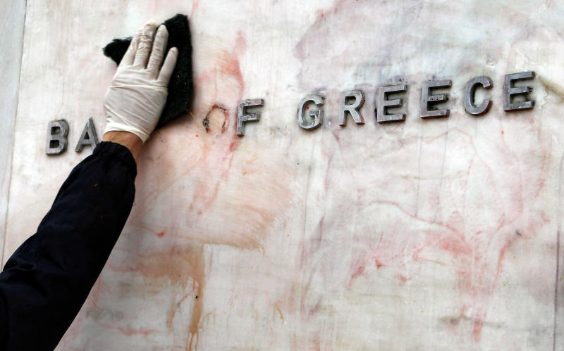 This Tuesday, Feb. 14, 2012 file photo, shows a worker cleaning a sign for the Bank of Greece from red and black paint, after Sunday's riots, in Athens. Austerity has been the main prescription across Europe for dealing with the continent's nearly 3-year-old debt crisis, brought on by too much government spending. Greece, one of three eurozone nations to need an international bailout, has cut spending on just about everything it can public sector salaries, pensions, education, health care and defense. (AP Photo/Thanassis Stavrakis)