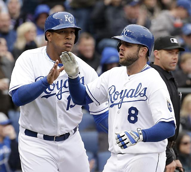 Kansas City Royals' Salvador Perez (13) and Mike Moustakas (8) celebrate after scoring on single hit by Lorenzo Cain during the fifth inning of a home opener baseball game against the Chicago White Sox, Friday, April 4, 2014, in Kansas City, Mo. (AP Photo/Charlie Riedel)