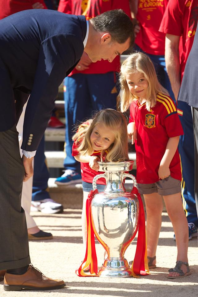 MADRID, SPAIN - JULY 02: Prince Felipe of Spain (L), Princess Leonor of Spain (C) and Princess Sofia of Spain (R) look at the UEFA EURO 2012 trophy as King Juan Carlos I of Spain receives the players of the victorious Spain team at Zarzuela Palace on July 2, 2012 in Madrid, Spain. (Photo by Pool/Getty Images)
