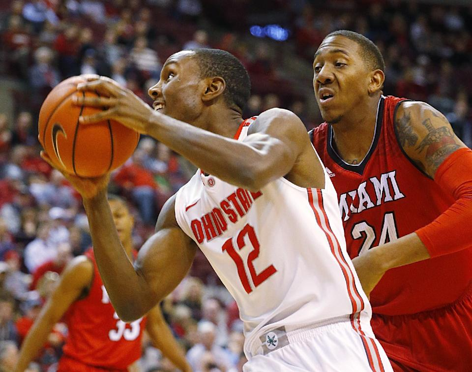 Ohio State's Sam Thompson (12) eyes the basket as he goes around Miami's Chris Bryant (24) in the first half of an NCAA basketball game, Monday, Dec. 22, 2014, in Columbus, Ohio. (AP Photo/Mike Munden)