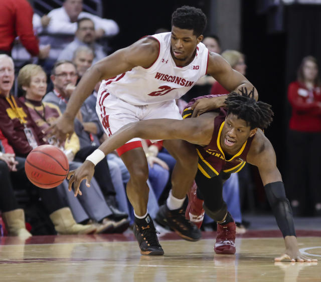 Wisconsin's Khalil Iverson (21) and Minnesota's Daniel Oturu (25) go after a loose ball during the second half of an NCAA college basketball game Thursday, Jan. 3, 2019, in Madison, Wis. Minnesota won 59-52. (AP Photo/Andy Manis)