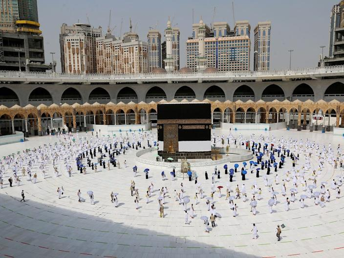 Pilgrims, some holding colored umbrellas, walk along matching colored rings that separate them in the holy city of Mecca, Saudi Arabia, on July 29, 2020.