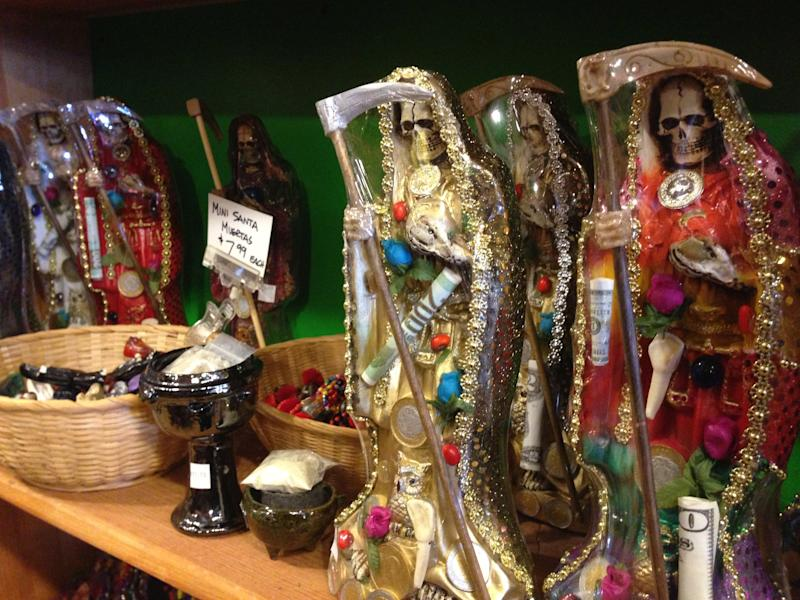 "FILE - In this Feb. 13, 2013 file photo, statues of La Santa Muerte are shown at the Masks y Mas art store in Albuquerque, N.M. As ""Breaking Bad"" finishes filming its fifth and final season in Albuquerque, the popularity of the show is providing a boost to the economy and creating a dilemma for local tourism officials as they walk the fine line of profiting from a show that centers around drug trafficking, addiction and violence. The store provided the statues used in the chilling opening scene of the show's third season, in which a pair of cartel assassins crawl to the saint's shrine in Mexico to request some divine help. (AP Photo/Russell Contreras, File)"