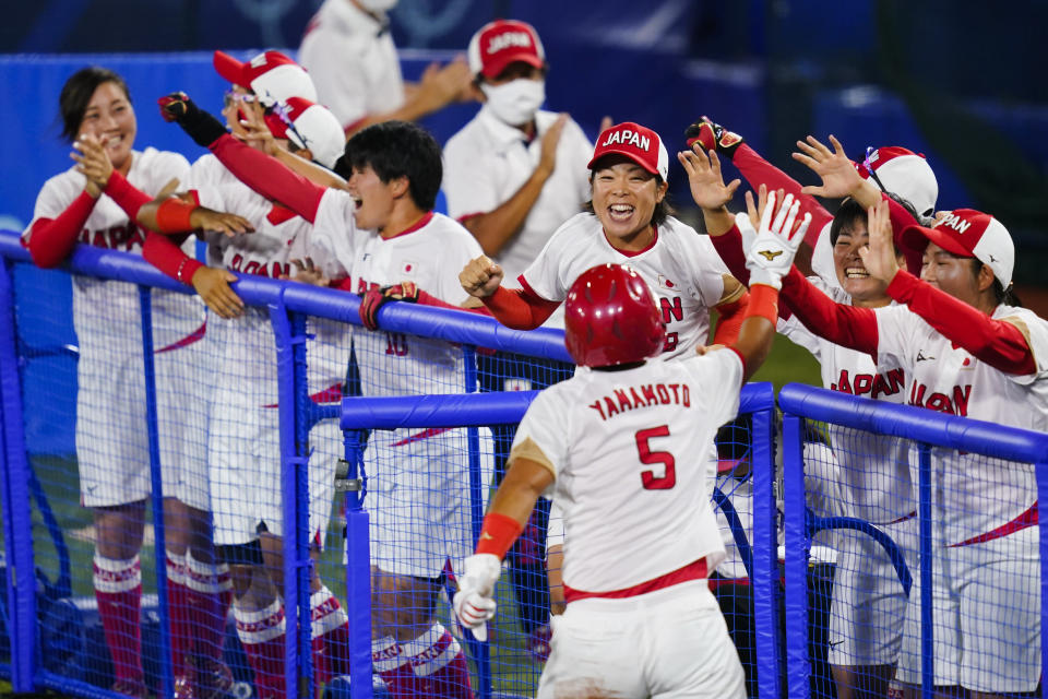 Japan's Yu Yamamoto (5) celebrate with teammates after scoring on a single in the fifth inning of a softball game against the United States at the 2020 Summer Olympics, Tuesday, July 27, 2021, in Yokohama, Japan. (AP Photo/Matt Slocum)