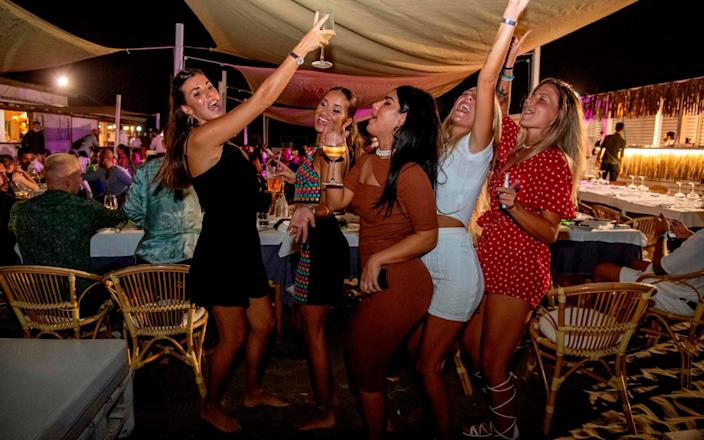 Young women at a beach club in Fregene near Rome, before the government closed nightclubs and discos - AFP