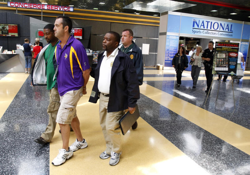 Steve Jensen, 40, of Osseo, Minn., the head of Minnesota-based Vintage Sports Authentics, is escorted by U.S. postal inspectors from the National Sports Collectors Convention in Rosemont, Ill., Thursday, Aug. 4, 2011, after his arrest for allegedly selling fake sports jerseys that his company says were worn by athletes during games.    Postal inspectors are also searching the company's warehouse in Plymouth, Minn., looking for other merchandise that could be phony. They allege the scheme has been going on for about four or five years.  (AP Photo/Kamil Krzaczynski)