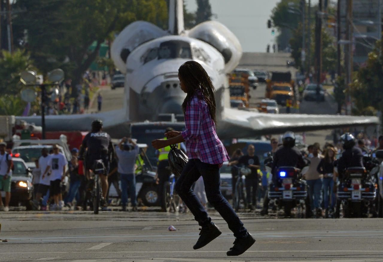 A young woman runs across the street in front of the space shuttle Endeavour as it is slowly moved down Crenshaw Blvd., Saturday, Oct.13, 2012, in Los Angeles. The shuttle is on its last mission — a 12-mile creep through city streets. It will move past an eclectic mix of strip malls, mom-and-pop shops, tidy lawns and faded apartment buildings. Its final destination: California Science Center in South Los Angeles where it will be put on display. (AP Photo/Mark J. Terrill)