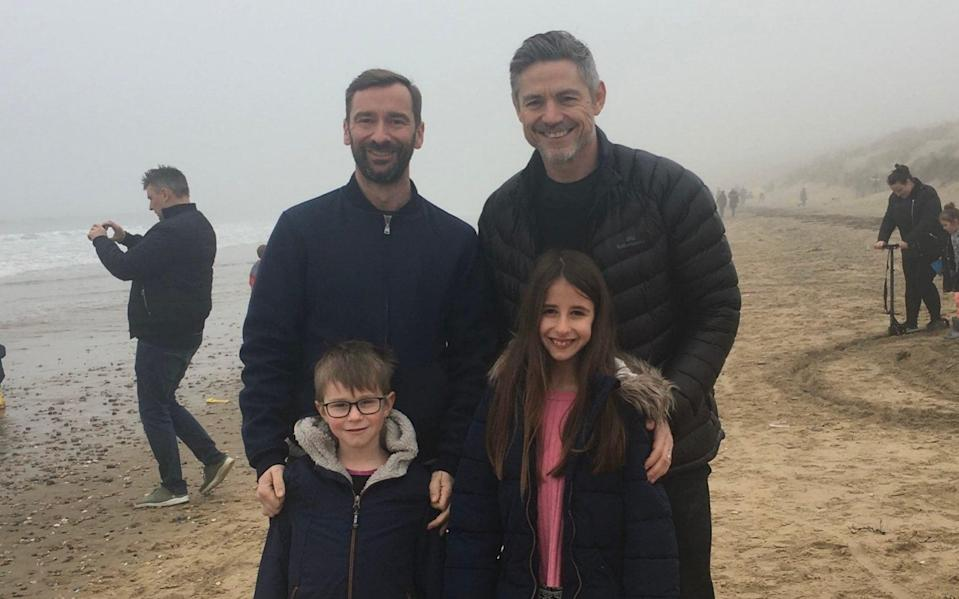 Charlie Condou, his husband, Cam, and children Georgia and Hal, enjoy a stroll on the beach - Charlie Condou
