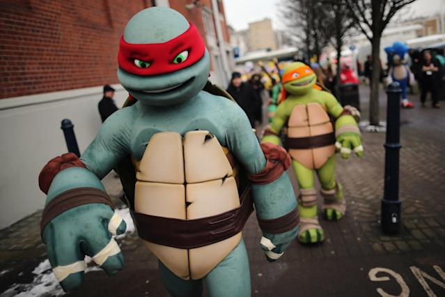LONDON, ENGLAND - JANUARY 22: Life size Teenage Mutant Ninja Turtles cartoon characters are led outside for a photocall during the 2013 London Toy Fair at Olympia Exhibition Centre on January 22, 2013 in London, England. The annual fair which is organised by the British Toy and Hobby Association, brings together toy manufacturers and retailers from around the world. (Photo by Dan Kitwood/Getty Images)
