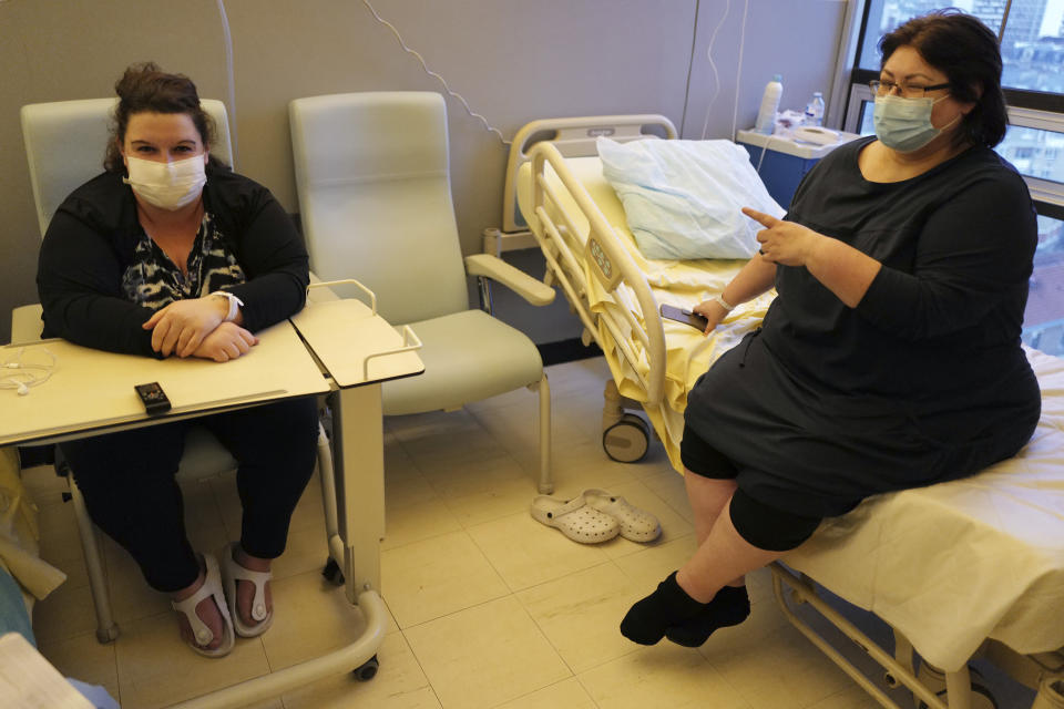 Lolita Andela, left, who works as a carer for a disabled man and Caroline Erganian, a retired secretary, chat in their room on the eve of their surgery at Bichat Hospital, AP-HP, in Paris Tuesday, Dec. 1, 2020. Hospitals are increasingly grappling with giant backlogs of surgeries that were postponed when COVID-19 hit. To prevent the collapse of their public health systems, countries hard-hit by the virus in Europe prioritized virus patients and put off nonessential procedures, and even some essential ones. (AP Photo/Francois Mori)
