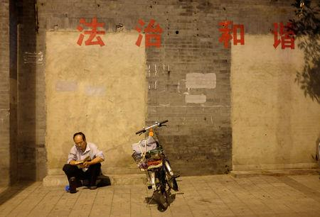 "FILE PHOTO: A resident sits near his bicycle while reading a book against a wall with the political slogans ""Rule of law (L) and Harmony "" in central Beijing, China August 18, 2014. REUTERS/Jason Lee/File photo"