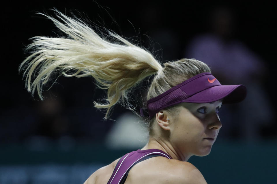 Elina Svitolina of the Ukraine plays a return shot while competing against Caroline Wozniacki of Denmark during their women's singles match at the WTA tennis finals in Singapore, Thursday, Oct. 25, 2018. (AP Photo/Vincent Thian)