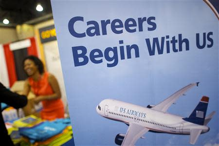 A recruiter for Cigna greets a job seeker behind a poster advertising employment opportunities with US Airways, at a career fair in Philadelphia, in this file photo taken July 25, 2013. U.S. private employers added 176,000 jobs in August, nearly matching economists' expectations for the month, a report by a payrolls processor showed on Thursday. REUTERS/Mark Makela/Files