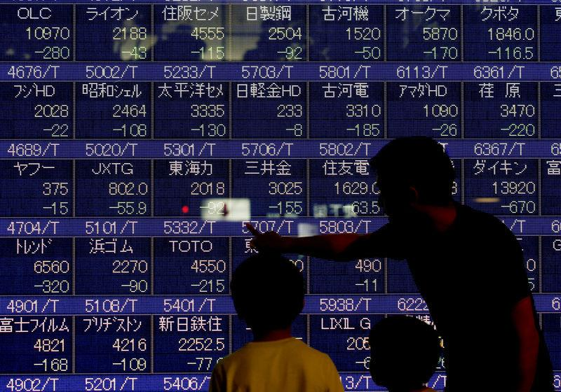 A man talks to his children in front of an electronic stock quotation board outside a brokerage in Tokyo
