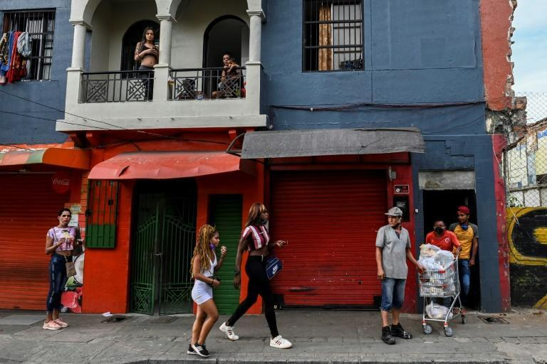 People walk outside a low-cost hotel where prostitutes live and work in Medellin, Colombia (AFP Photo/Joaquin SARMIENTO)