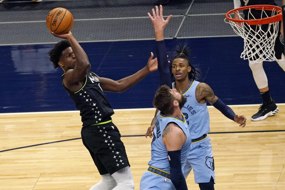 Minnesota Timberwolves' Anthony Edwards, left, shoots over Memphis Grizzlies' Jonas Valanciunas, center, during the first half of an NBA basketball game Wednesday, May 5, 2021, in Minneapolis. (AP Photo/Jim Mone)