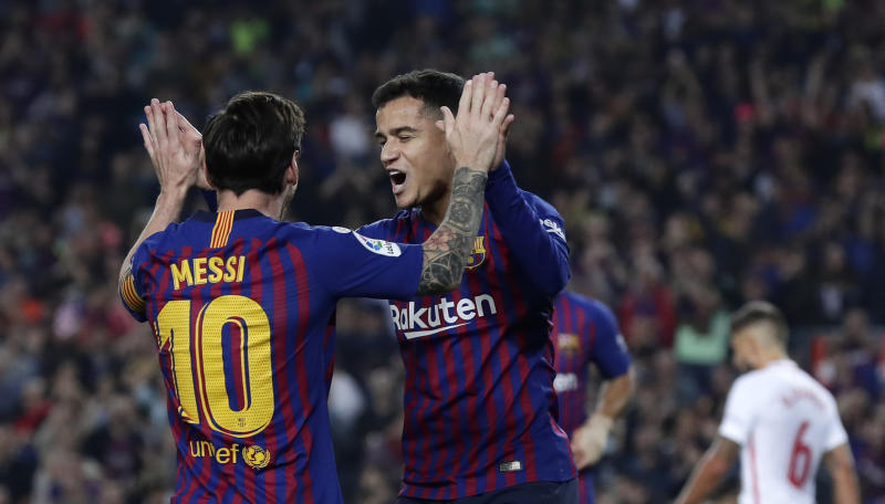 FC Barcelona's Coutinho, right, celebrates after scoring with his teammate Lionel Messi during the Spanish La Liga soccer match between FC Barcelona and Sevilla at the Camp Nou stadium in Barcelona, Spain, Saturday, Oct. 20, 2018. (AP Photo/Manu Fernandez)