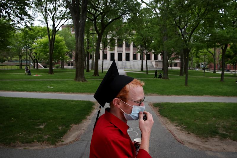 CAMBRIDGE, MA - MAY 28: Harvard Law School graduate Jesse Burbank spends time on campus before attending the online graduation ceremony in his room in Cambridge, MA on May 28, 2020. As a proctor Burbank was able to remain on campus. He earned a Juris Doctor from Harvard Law School. Harvard University postponed its commencement exercises and held an online event Thursday amid the coronavirus pandemic. Harvard, like legions of other colleges nationwide, told students in March not to return to campus after spring break ended and to take their classes online. The last time the university was forced to pivot midway through the year was in the 1940s, in the midst of World War II, when the campus was given over to military training. (Photo by Craig F. Walker/The Boston Globe via Getty Images)