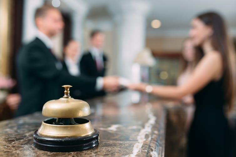 Gold bell at a hotel reception with guests and hotel employees in the background