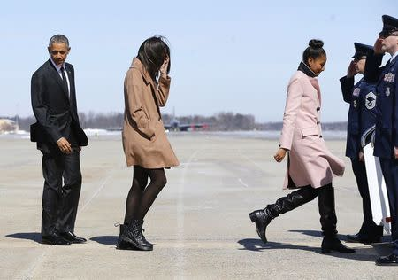 (L-R) U.S. President Barack Obama and daughters Malia and Sasha are saluted as they board Air Force One for travel to Alabama from Joint Base Andrews, Maryland March 7, 2015. REUTERS/Jonathan Ernst